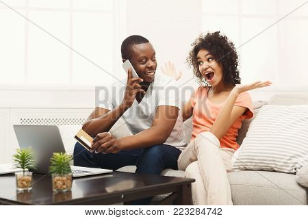 Young couple web surfing on laptop sitting on sofa at home, man talking on phone, relaxing. Freelance, remote work and online shopping concept, copy space