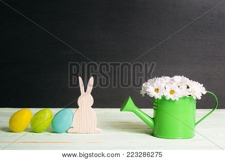 Easter bunny and eggs with daisies bouquet - Easter painted eggs leaned against a wooden bunny and a green watering can full of white daisies, on a table, with a black wall, on a sunny day.