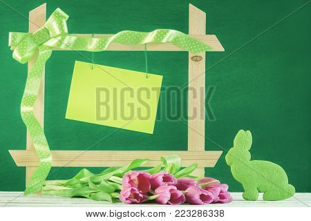 Frame with paper note and tulips - Easter greeting card with a wooden frame decorated with green ribbon, a blank message card and pink tulips and a bunny shaped green cookie.