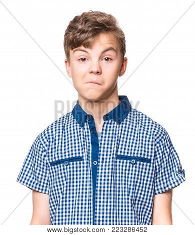 Teen boy making silly grimace - funny surprised face. Playful child isolated on white background. Emotional portrait of caucasian teenager looking at camera.