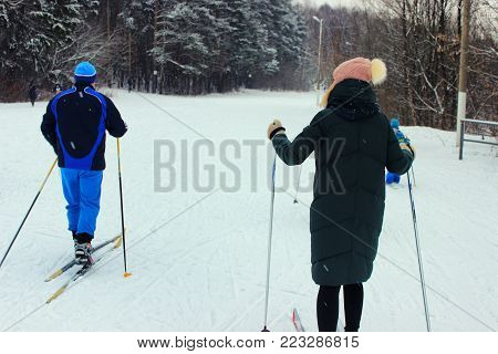 The man and young beautiful girl go skiing in winter on a ski slope.