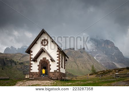 A woman in a yellow raincoat standing infront of the Chapel at Rolle Pass, one of the oldest roads in the Dolomites. The road connects the valleys of Fiemme and Primiero.