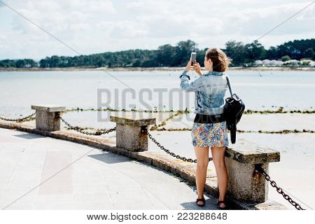 Young woman taking a photo on smartphone of the seascape, O Grove island, Galicia, Spain. Female traveler standing on pier and taking photo of the opposite shore of the bay