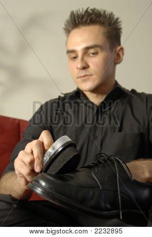 Young Man Polishing A Shoe