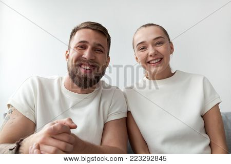 Smiling young couple with happy faces looking at web camera, man and woman making videocall to distance friend by skype, funny vloggers recording videoblog or video message, webcam view portrait poster