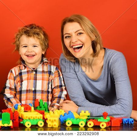 Woman And Boy Play On Red Background.
