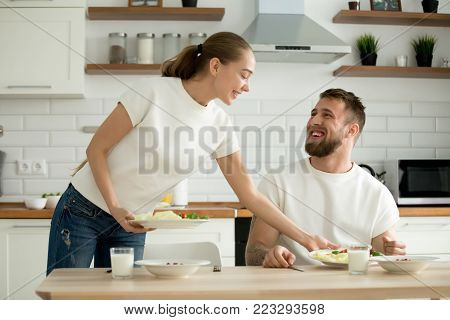 Attractive caring wife serving food cooked for husband in cozy kitchen, grateful man appreciating woman prepared healthy breakfast dinner, happy couple enjoying meal together at home dining table