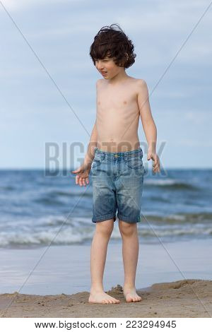 A guy in denim shorts is happy on the sandy beach of the sea.