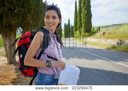 Hiker Girl Hitchhiking by the Side of the Road
