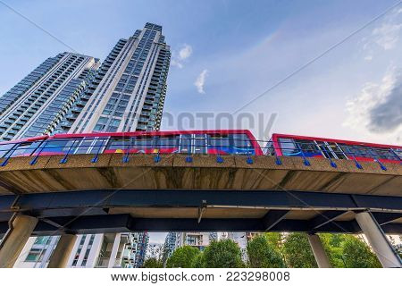 LONDON, UNITED KINGDOM - OCTOBER 07: Docklands light railway train passing by Canary Wharf high rise buildings in South Quay on October 07, 2017 in London