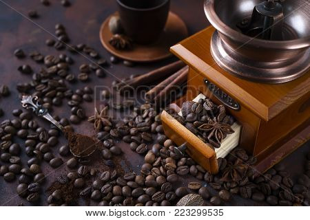 retro coffee grinder with cup and beans on srone dark background