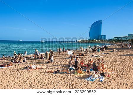BARCELONA, SPAIN - September 14, 2017:  Sandy Barceloneta beach in Barcelona with W hotel on a background and people enjoying a sunny day