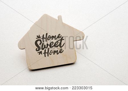 wooden house with written text over white paper background, home sweet home concept