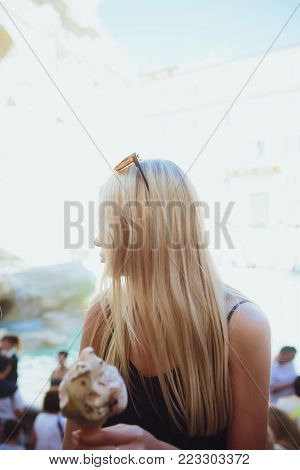 Ice cream, young beautiful blond girl in a bright outfit gets pleasure from ice cream. Tastes like a yellow Eskimo. Having fun. Indoor. White background. A girl licks ice cream on a background of a fountain of a treasure