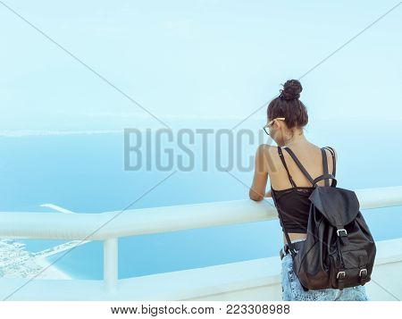Fashion young girl with backpack in casual clothes glasses enjoying a view from the mountain to the sea. Tourist traveler standing on viewing platform of hotel agaist blue background valley landscape view mockup for text. Attractive slim brunette mixed ra