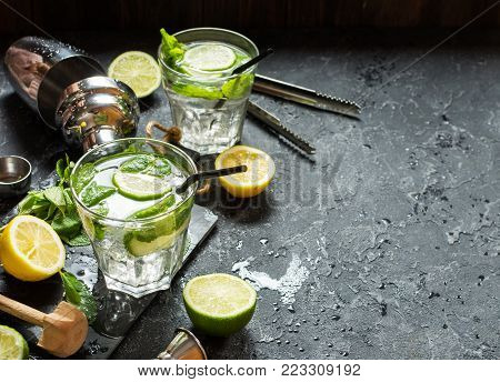 Mojito cocktail with lime and mint in highball glass on a stone table. Drink making tools and ingredients for cocktail. Copy space