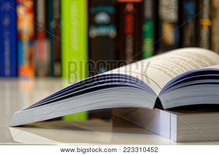 Open book lying on a white table and colorful books in a row in background
