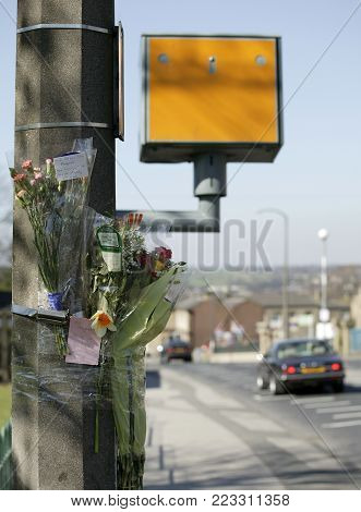 HECKMONDWIKE, WEST YORKSHIRE, UK: FLOWERS LEFT AT SIGHT OF ROAD ACCIDENT NEAR SPEED CAMERA, CIRCA 2003, HECKMONDWIKE, WEST YORKSHIRE, UK