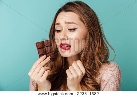 Portrait of a puzzled brown haired woman with bright makeup eating chocolate bar isolated over blue background