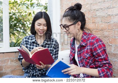 Young Asian Woman Resding Book Together. Woman Holding Book With Attractive Smiling Together. People