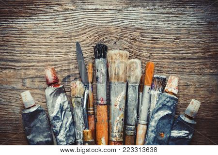 Artist paintbrushes, paint tubes and palette knife closeup on old wooden background, retro stylized. Copy space for text.