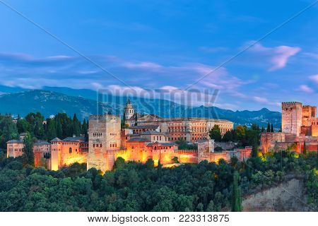 Palace and fortress complex Alhambra with Comares Tower, Palacios Nazaries and Palace of Charles V during evening blue hour in Granada, Andalusia, Spain