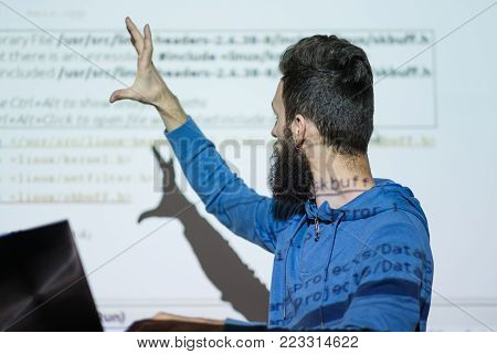 University reading. Teacher delivering a lecture on computer studies and shows and important piece of information with his hand. Education concept