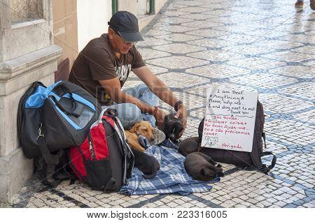 LISBON, PORTUGAL - 05.21.2017: urban city street beggar with dogs