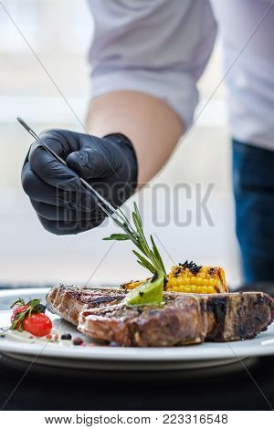 food stylist at work. Decorating meat steak meal. Culinary art. Creative arrangement
