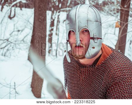 Medieval viking warrior in chain mail and helmet holds a spear in the winter forest
