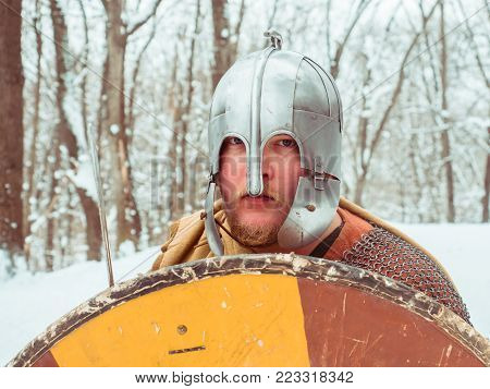 Medieval Irish warrior in chain mail and helmet holds a shield in the winter forest