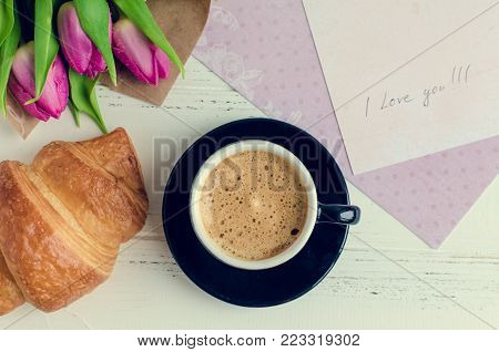 Cup of coffee with croissant, bouquet of pink tulips and notes I LOVE YOU on white shabby chic background. Romantic Valentines morning concept. Valentine's day breakfast. Top view.