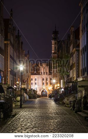 View of old buildings on the empty St. Mary's Street (ul. Mariacka) and St. Mary's Gate (Brama Mariacka) at the Main Town (Old Town) in Gdansk, Poland, in the evening.