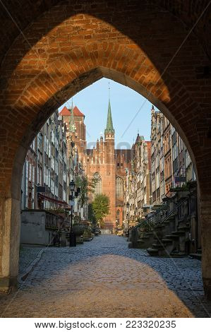 Old buildings on the St. Mary's Street (ul. Mariacka) and St. Mary's Church at the Main Town (Old Town) in Gdansk, Poland, viewed through an arched gateway in the morning.