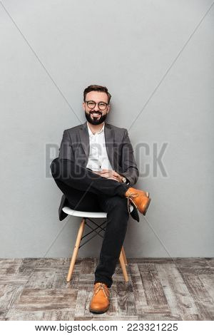Full-length portrait of relaxed man in casual sitting on chair in office and smiling on camera isolated over gray background