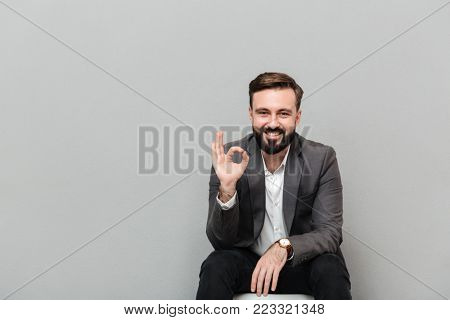 Closeup portrait of cheerful guy showing OK sign while resting on chair in office being satisfied isolated over gray background