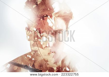 Irresistible look. Handsome young concentrated guy looking straight while posing on the white background and reflecting