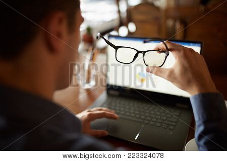 Back view of man hand holding eyeglasses in front of laptop screen with charts and diagrams. Poor eyesight threatment theme. Computer glasses.
