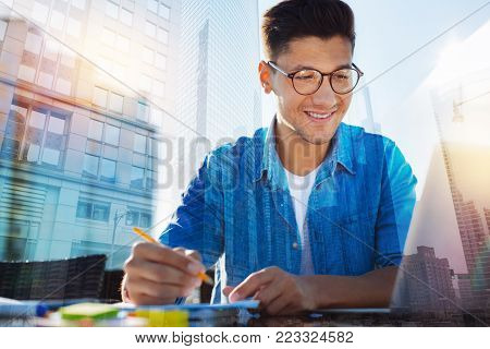 In high spirits. Handsome exuberant young man wearing glasses and holding a pencil and smiling