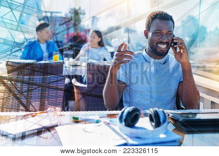 Happy to hear. Attractive exuberant afro-american man smiling and talking on his phone while sitting at the table and his stuff lying on it