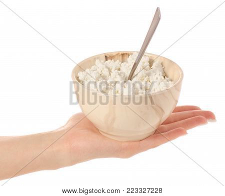 Bowl of cottage cheese with spoon in hand isolated on white background isolation