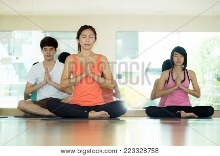 Group of asian women and man practicing yoga, fitness stretching flexibility pose, working out, healthy lifestyle, wellness, well being