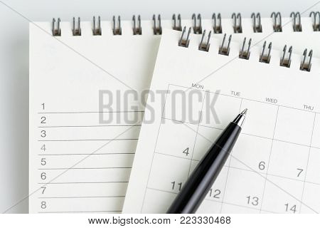 Personal yearly to do lists or new year's resolution or plan concept by clean calendar and  list of numbers on white notepad with pen on it.