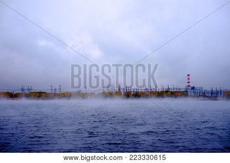 River near a nuclear power plant. Beautiful views of autumn landscape near a nuclear power plant - the river along which a fog is rising, away station and covered with the autumn colors of the trees.