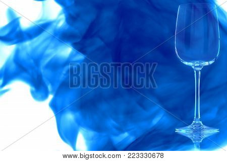 Empty white wine glass on white background enveloped in puff of blue smoke.
