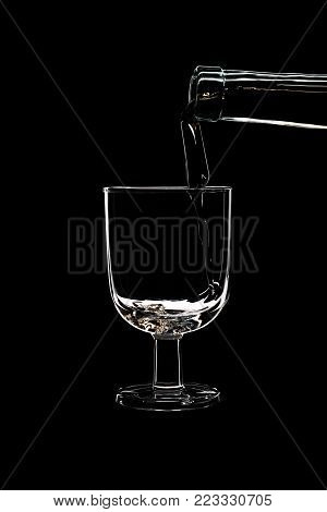 A low glass of white wine is pouring wine from a bottle of white. Filmed in close-up glass, where you pour the wine from the bottle.