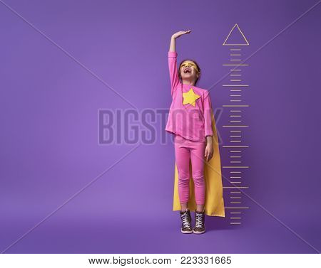 Little child is playing superhero. Kid is measuring the growth on the background of bright ultraviolet wall. Girl power concept. Yellow, pink and  purple colors.