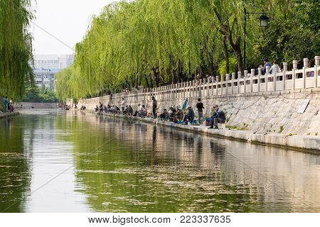 April 2015 - Jinan, China - local people fishing in the City moat running around the old city of Jinan, connecting Daming Lake, Quancheng Square and the famous Baotou Spring