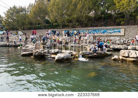 April 2015 - Jinan, China - local people taking water from one of the many springs of the City moat of Jinan, which connects Daming Lake, Quancheng Square and the famous Baotou Spring