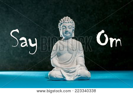 Say Om - Little Buddha statue, meditation, zen and relax yoga concept.